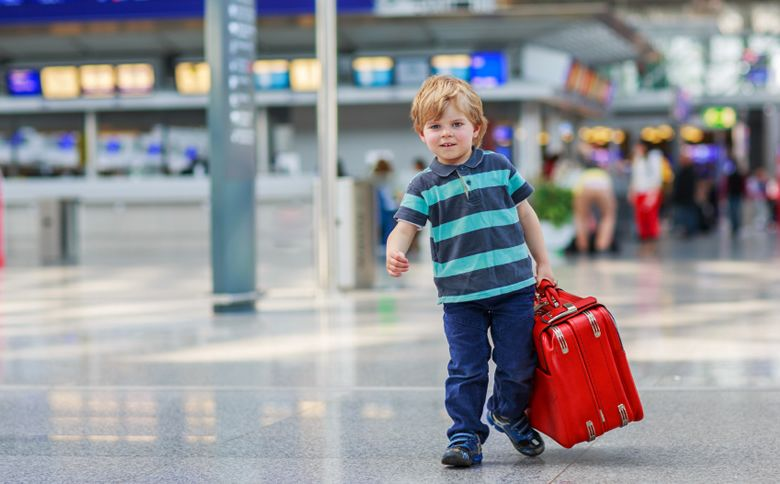 Smiling child at airport with luggage ready for holiday