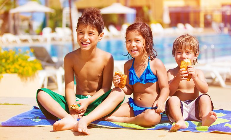 Happy children on holiday eating ice creams
